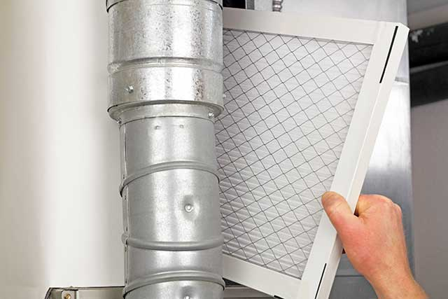 Furnace filter being replaced