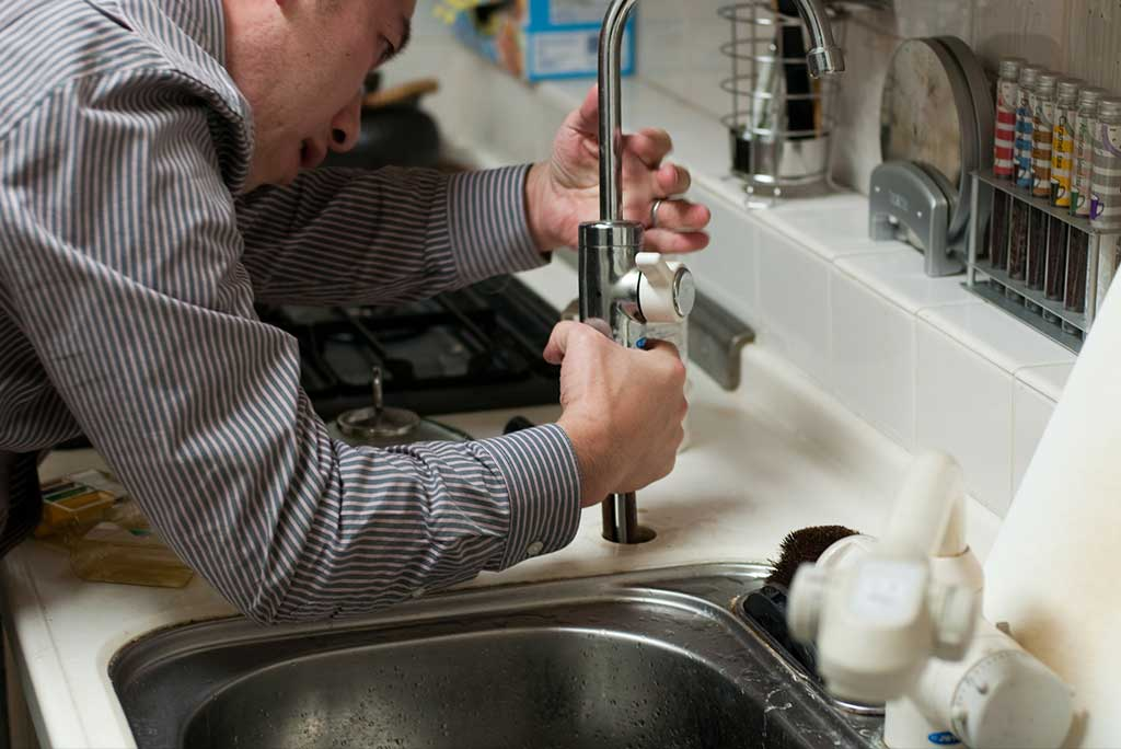 Plumber fixing a sink faucet