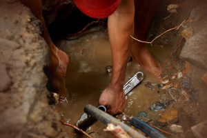 Plumber fixing piping in ground