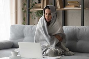 Woman wrapped in blanket in a cold home