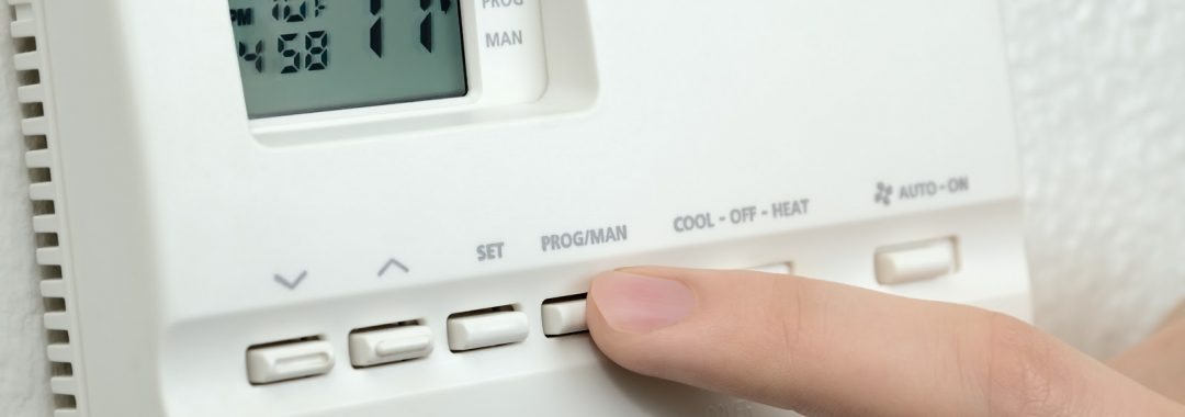 Woman testing an old thermostat